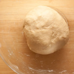 Bread dough for making bath buns after kneading. The dough is in a bowl ready for the first rising.
