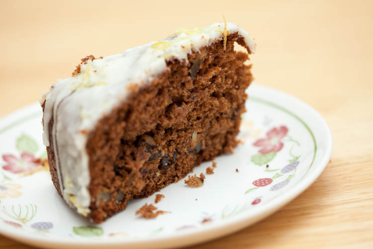 A slice of Iced Date & Walnut Cake on a plate