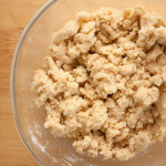 Ingredients for Grantham Gingerbread mixed together to form a dough. The mixture is in a glass bowl on a wooden surface.