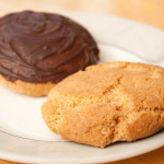 Two Grantham Gingerbread biscuits / cookies on a plate. One of the gingerbreads has been coated with dark chocolate on top.